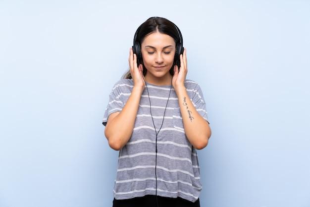 Młoda Brunetki Kobieta Nad Odosobnioną Błękit ścianą Słucha Muzyka Z Hełmofonami Premium Zdjęcia