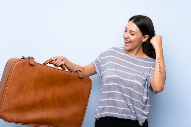 Młoda brunetki kobieta nad odosobnioną błękit ścianą trzyma rocznik teczkę Premium Zdjęcia