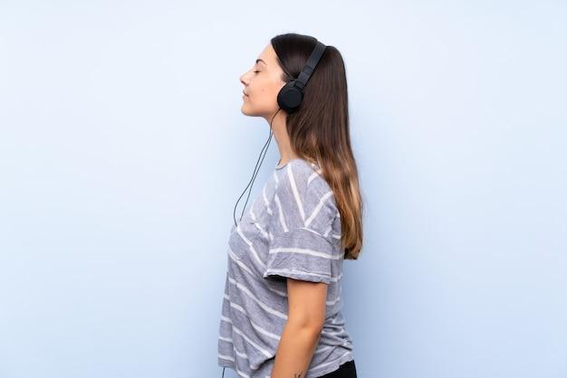 Młoda brunetki kobieta słucha muzyka z hełmofonami Premium Zdjęcia