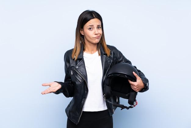 Młoda Brunetki Kobieta Trzyma Motocyklu Hełm Nad Błękit ścianą Robi Wątpliwość Gestowi Podczas Gdy Podnoszący Ramiona Premium Zdjęcia
