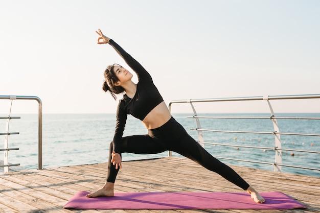 Młoda Brunetki Kobieta W Czarnego Kombinezonu ćwiczy Joga Na Plaży Przy Wschodem Słońca. Pojęcie Wellness I Zdrowego Stylu życia. Premium Zdjęcia