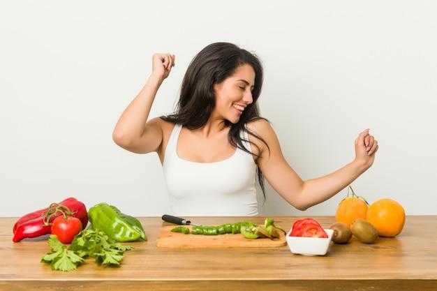Młoda bujna kobieta przygotowuje zdrowy posiłek, taniec i zabawę. Premium Zdjęcia