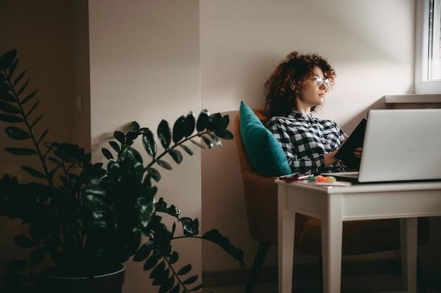 Młoda Businesswoman Z Kręconymi Włosami I Okularami, Pracując W Domu Przy Komputerze, Myśląc O Czymś, Trzymając Książkę Premium Zdjęcia