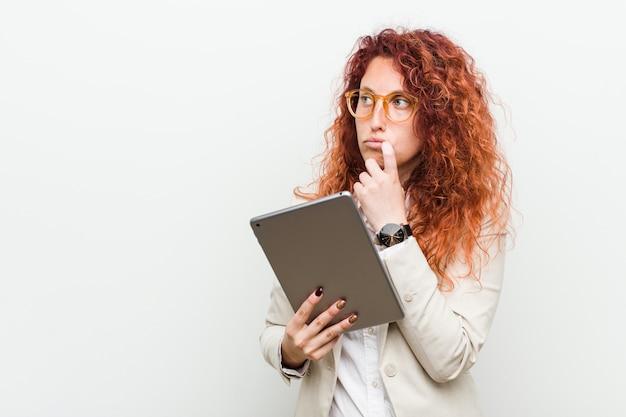 Młoda caucasian biznesowa rudzielec kobieta trzyma pastylkę relaksował myśleć o coś patrzeje odbitkową przestrzeń Premium Zdjęcia