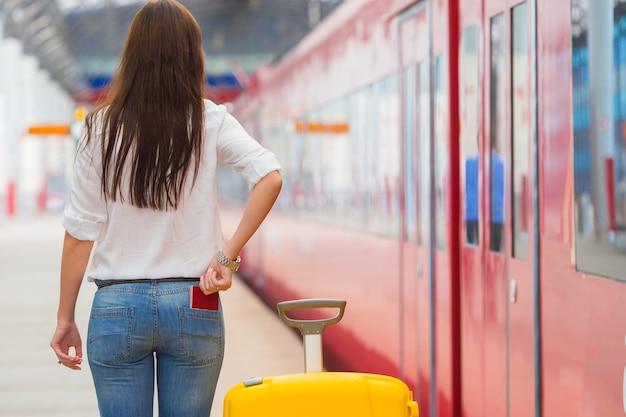 Młoda caucasian dziewczyna z bagażem przy stacyjnym podróżowaniem pociągiem Premium Zdjęcia