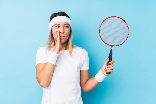 Młoda Caucasian Kobieta Bawić Się Badminton Odizolowywającego Mówi Sekretną Gorącą Hamującą Wiadomość I Patrzeje Na Boku Premium Zdjęcia