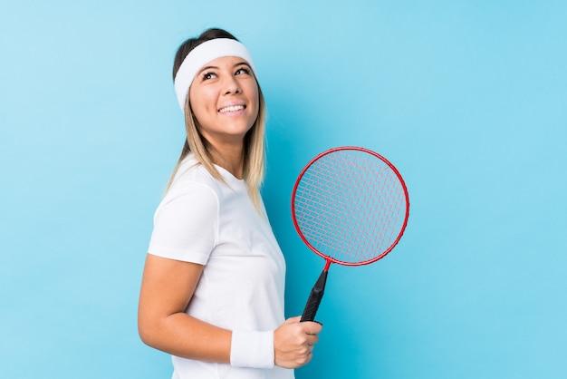 Młoda Caucasian Kobieta Bawić Się Badminton Odizolowywającego Patrzeje Na Boku Uśmiechniętych, Rozochoconych I Przyjemnych. Premium Zdjęcia