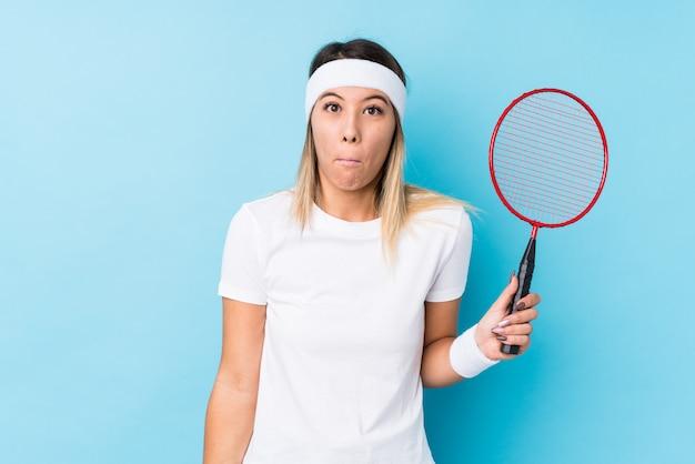 Młoda Caucasian Kobieta Bawić Się Badminton Odizolowywającego Wzrusza Ramionami Ramiona I Otwiera Oczy Zmieszanych. Premium Zdjęcia