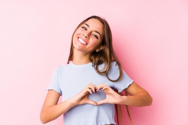 Młoda Caucasian Kobieta Jest Ubranym Narciarskich Ubrania Odizolowywał Uśmiecha Się Kierowego Kształt I Pokazuje Z Rękami. Premium Zdjęcia