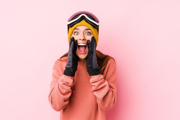 Młoda Caucasian Kobieta Jest Ubranym Narciarskiego Ubrania Odizolowywał Krzyczeć Excited Przód. Premium Zdjęcia