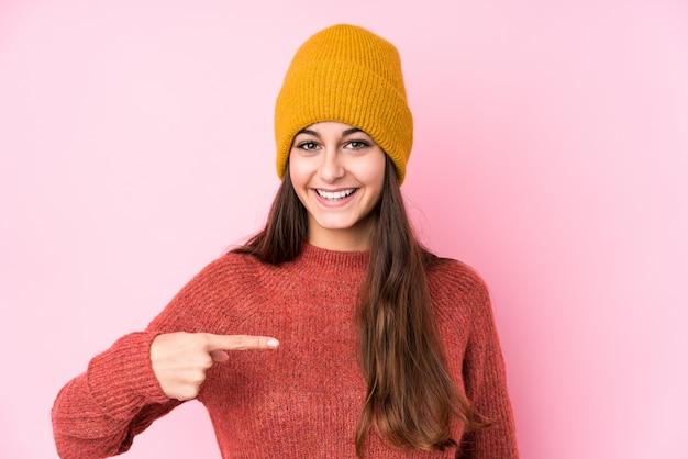 Młoda Caucasian Kobieta Jest Ubranym Wełnianej Nakrętki Osoby Wskazuje Ręcznie Do Koszula Kopii Przestrzeni, Dumny I Ufny Premium Zdjęcia