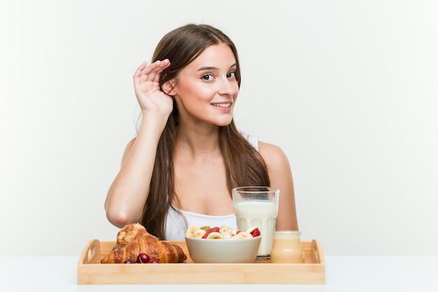 Młoda caucasian kobieta ma śniadanie próbuje słuchać plotki. Premium Zdjęcia
