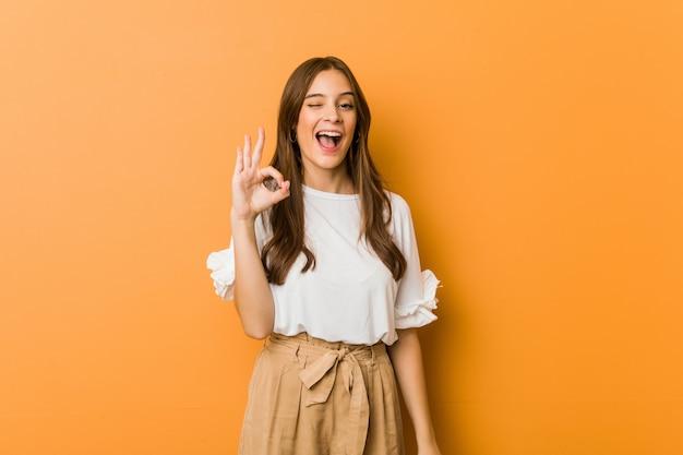 Młoda caucasian kobieta mruga okiem i trzyma w porządku gest ręką. Premium Zdjęcia