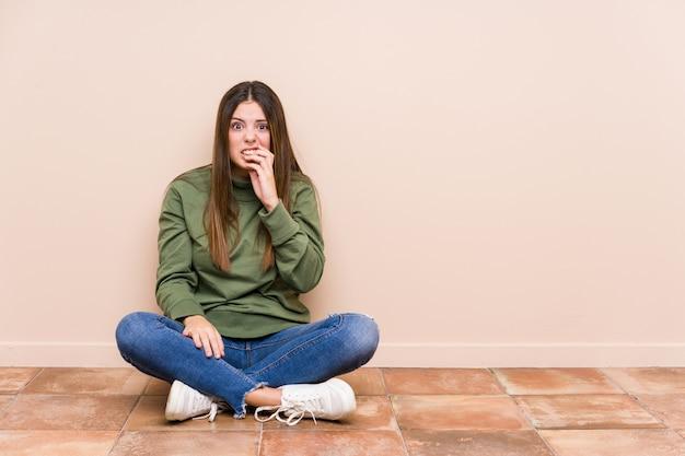 Młoda Caucasian Kobieta Siedzi Na Podłoga Odizolowywał Gryzących Paznokcie, Nerwowych I Bardzo Niespokojnych. Premium Zdjęcia