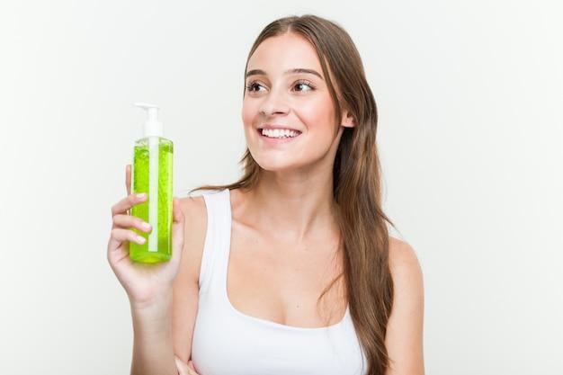 Młoda caucasian kobieta trzyma aloesu butelki ono uśmiecha się ufny z krzyżować rękami. Premium Zdjęcia