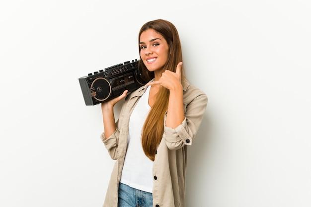 Młoda caucasian kobieta trzyma guetto niszczyciela pokazuje telefonu komórkowego wezwania gest z palcami. Premium Zdjęcia