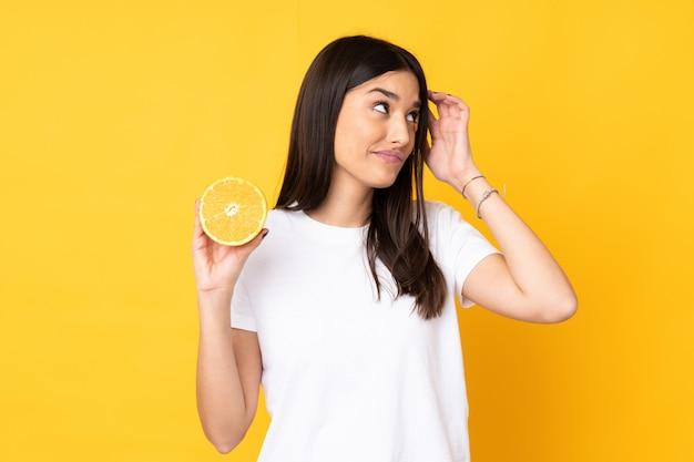 Młoda Caucasian Kobieta Trzyma Pomarańcze Na Kolor żółty ścianie Ma Wątpliwości I Z Zmieszanym Wyrazem Twarzy Premium Zdjęcia