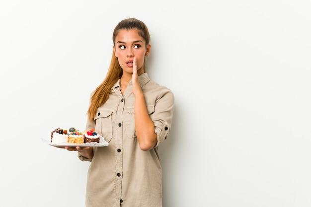 Młoda caucasian kobieta trzyma słodkich ciastka mówi sekretną gorącą wiadomość dnia Premium Zdjęcia