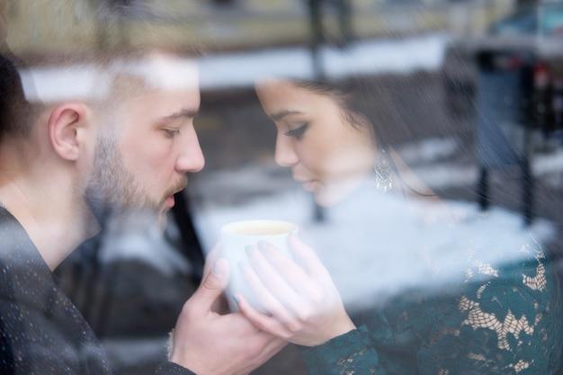 Młoda Caucasian Para Sittiing Blisko Okno I Trzyma Filiżankę Herbata Premium Zdjęcia