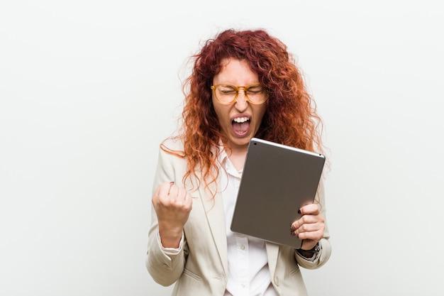 Młoda caucasian rudzielec biznesowa kobieta trzyma pastylkę rozwesela beztroski i podekscytowany Premium Zdjęcia