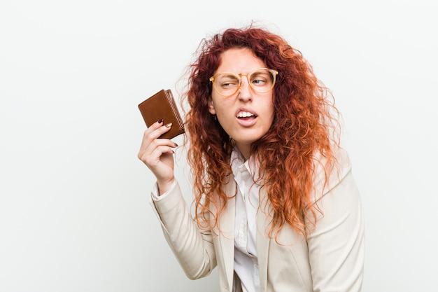 Młoda caucasian rudzielec kobieta trzyma portfel próbuje słuchać plotki Premium Zdjęcia