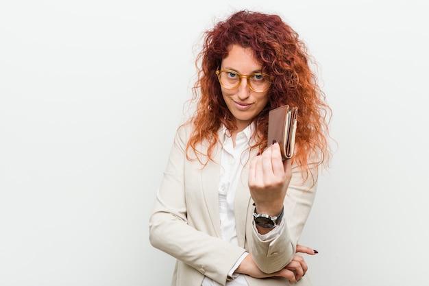 Młoda caucasian rudzielec kobieta trzyma portfel wskazuje z tobą palcem, jakby zapraszający zbliżał się Premium Zdjęcia