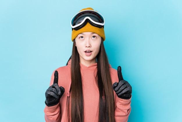 Młoda Chinka Na Sobie Ubrania Narciarskie Na Białym Tle, Wskazując Do Góry Z Otwartymi Ustami. Premium Zdjęcia
