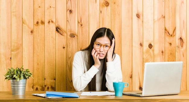 Młoda Chinka Studiująca Na Swoim Biurku Jęcząca I Płacząca Niepocieszona. Premium Zdjęcia