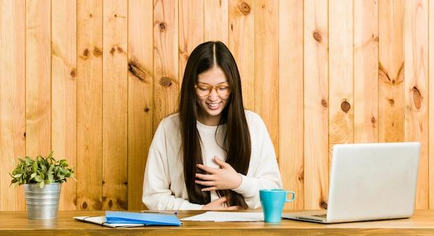 Młoda chinka studiuje na biurku, śmieje się radośnie i dobrze się trzyma, trzymając ręce na brzuchu. Premium Zdjęcia