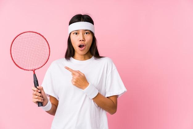 Młoda Chińska Kobieta Bawić Się Badminton W Różowym Tle Wskazuje Strona Premium Zdjęcia