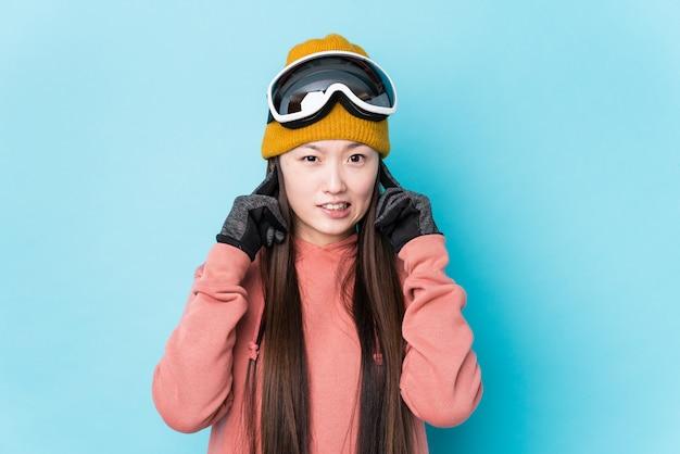 Młoda Chińska Kobieta Jest Ubranym Nart Ubrania Odizolowywał Nakrywkowych Ucho Z Rękami. Premium Zdjęcia