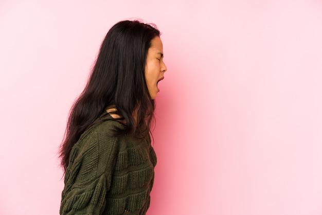 Młoda Chińska Kobieta Odizolowywająca Na Różowej ścianie Krzyczy W Kierunku Odbitkowej Przestrzeni Premium Zdjęcia