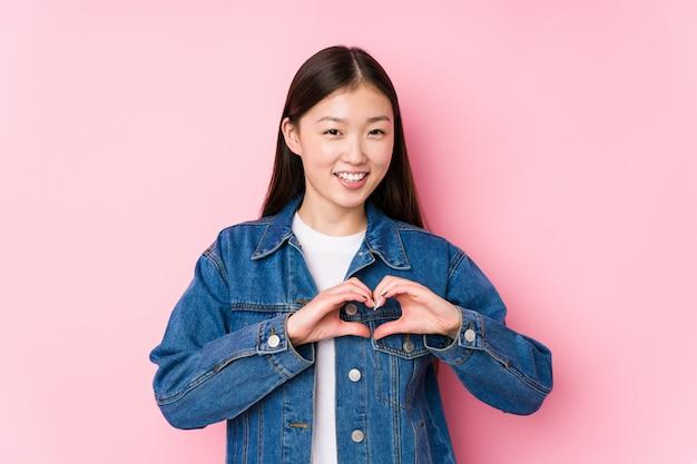 Młoda Chińska Kobieta Pozuje W Różowej ścianie Odizolowywał Uśmiecha Się Kierowego Kształt I Pokazuje Z Rękami. Premium Zdjęcia