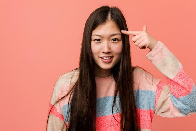Młoda Chłodno Chińska Kobieta Pokazuje Rozczarowanie Gest Z Palcem Wskazującym. Premium Zdjęcia