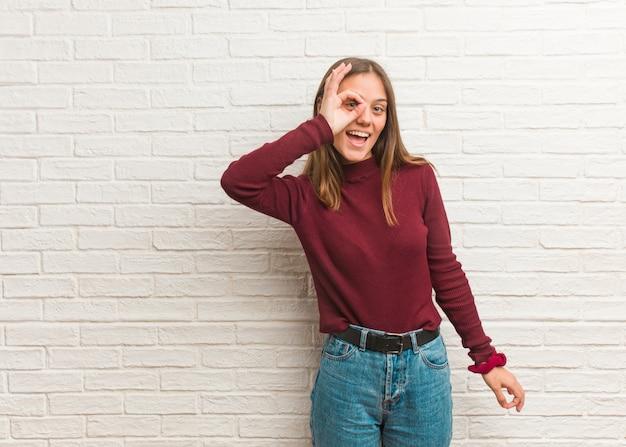 Młoda chłodno kobieta nad cegły ścianą ufną robi ok gestowi na oku Premium Zdjęcia