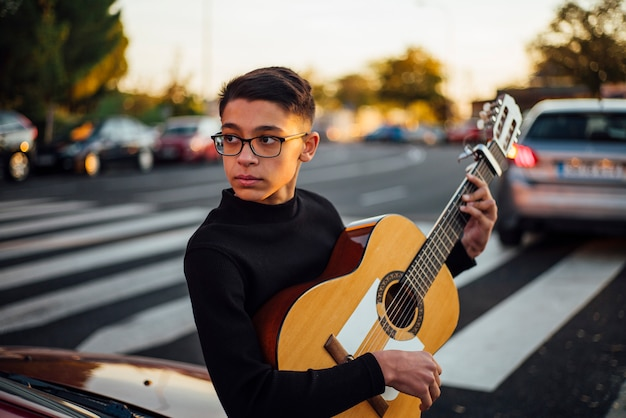 Młoda Chłopiec Bawić Się Gitarę Przez Miasta Madryt, Hiszpania. Premium Zdjęcia