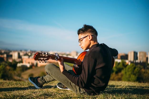 Młoda Chłopiec Bawić Się Gitarę W Mieście Madryt, Hiszpania W Tle. Premium Zdjęcia