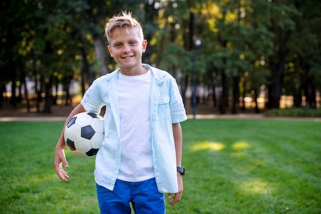 Młoda Chłopiec Patrzeje Kamerę Z Futbolową Piłką Darmowe Zdjęcia