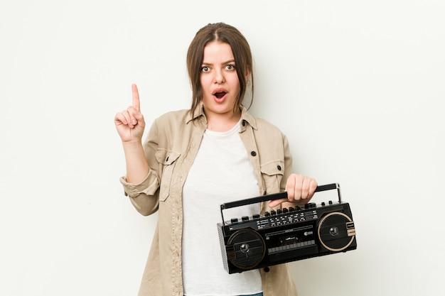 Młoda Curvy Kobieta Trzyma Retro Radio Ma Niektóre Doskonałego Pomysł, Pojęcie Twórczość. Premium Zdjęcia