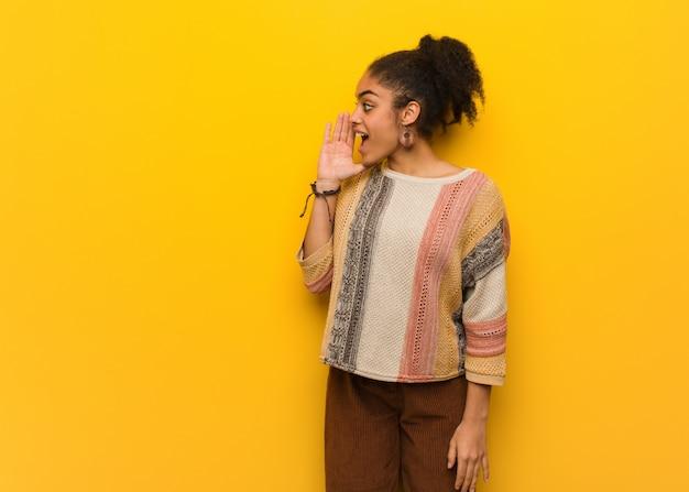 Młoda czarna amerykanin afrykańskiego pochodzenia dziewczyna z niebieskimi oczami szepcze plotki podtekst Premium Zdjęcia