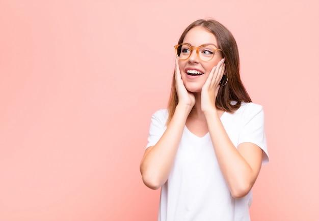 Młoda Czerwona Głowa Kobieta Czuje Się Szczęśliwa, Podekscytowana I Zaskoczona, Patrząc Z Boku Obiema Rękami Na Twarzy Na Płaskiej ścianie Premium Zdjęcia