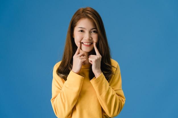 Młoda Dama Azji Pokazując Uśmiech, Pozytywne Wypowiedzi, Ubrana W Zwykły Materiał I Patrzeć Na Aparat Odizolowany Na Niebieskim Tle. Szczęśliwa Urocza Szczęśliwa Kobieta Raduje Się Z Sukcesu. Koncepcja Wyrazu Twarzy. Darmowe Zdjęcia