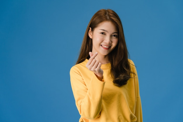 Młoda Dama Azji Z Pozytywnym Wyrazem Twarzy, Pokazuje Gest Rąk W Kształcie Serca, Ubrana W Zwykły Strój I Patrząc Na Aparat Na Białym Tle Na Niebieskim Tle. Szczęśliwa Urocza Szczęśliwa Kobieta Raduje Się Z Sukcesu. Darmowe Zdjęcia