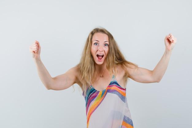 Młoda Dama Pokazuje Gest Zwycięzcy W Letniej Sukience I Wygląda Błogo Darmowe Zdjęcia