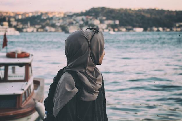 Młoda dama w hidżabie, patrząc na sae nad morzem. Darmowe Zdjęcia