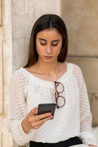 Młoda dama z szkłami na bluzce używać smartphone Darmowe Zdjęcia