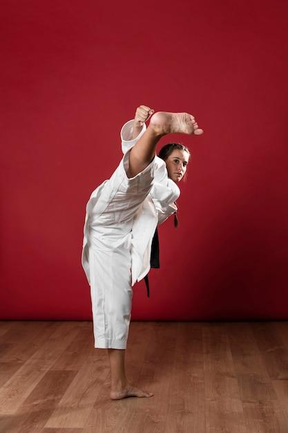 Młoda Dorosła Kobieta Z Czarnym Pasowym Wojownikiem Trenuje Karate Darmowe Zdjęcia