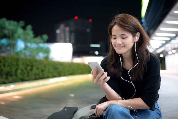 Młoda Dziewczyna Azjatyckich Słuchania Muzyki Lub Treści Wideo Za Pośrednictwem Telefonu Komórkowego Premium Zdjęcia