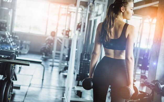 Młoda Dziewczyna Bawić Się Dumbbell ćwiczyć W Sprawności Fizycznej Premium Zdjęcia
