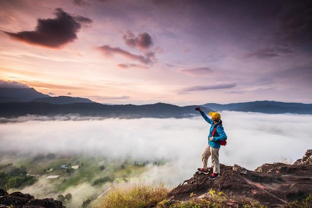 Młoda dziewczyna bierze fotografie morze mgła na wysokiej górze. Premium Zdjęcia
